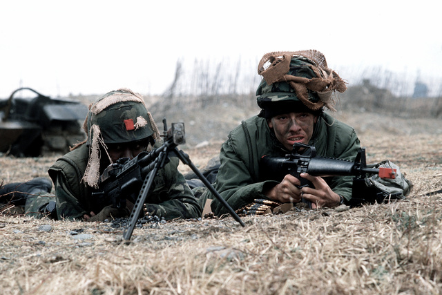 U.S. Marines operate M-60 machine guns, left, and an M-16 rifle, right, during Valiant Blitz, the amphibious assault landing phase of exercise Team Spirit '82