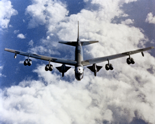 A high angle front view of a B-52H Stratofortress aircraft carrying a pair of D-21 drones while in flight