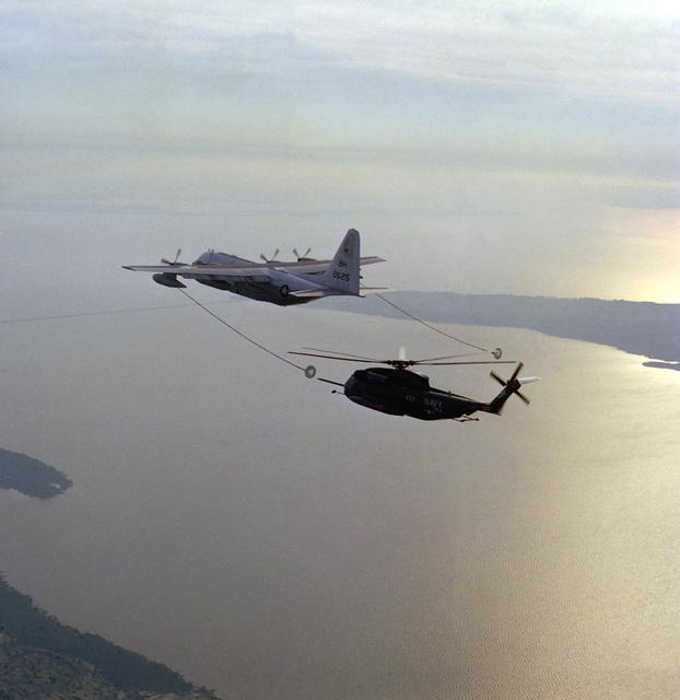 A left side view of a KC-130F Hercules aircraft from Marine Refueler-Transport Squadron 252 (VMGR-252) refueling an RH-53D Sea Stallion helicopter from Helicopter Mine Countermeasures Squadron 12 (HM-12)