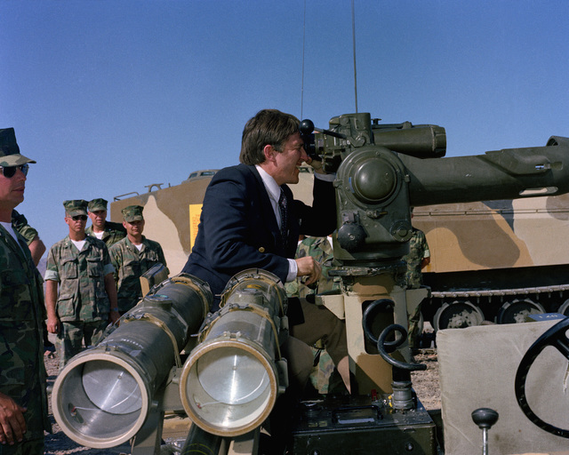 Secretary of the Navy John Lehman Jr. gets a chance to look through the sights of a heavy anti-tank weapon (TOW) during his tour of military installations. These Marines are participating in a CAX operation at the Marine Corps Air-Ground Combat Center