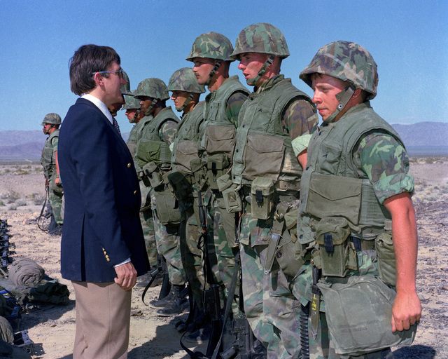 Secretary of the Navy John Lehman Jr. talks to a squad of Marines who are participating in a CAX operation at the Marine Corps Air-Ground Combat Center. The secretary is touring military installations