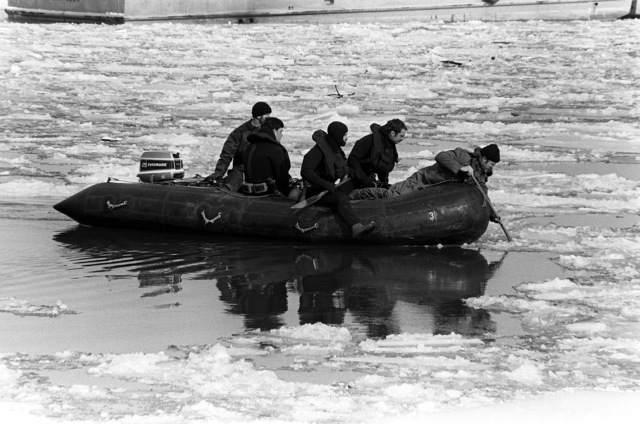 A Navy dive team navigates a rubber raft through the icy water searching for victims and wreckage from Flight 90, the Air Florida Boeing 737 that crashed into Rochambeau Bridge (14th Street). The divers are from the Explosive Ordnance Disposal School at Indian Head, Maryland and Harbor Clearance Unit Two, from Little Creek, Virginia