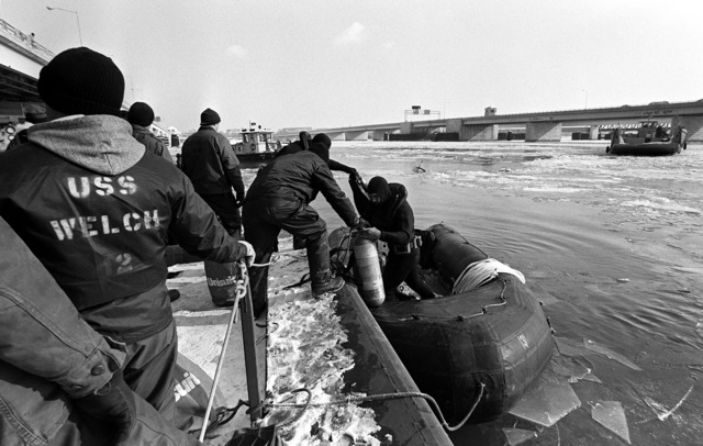 A Navy diver in scuba gear is assisted into a rubber raft before using it to locate to victims and wreckage from Flight 90, the Air Florida Boeing 737 that crashed into Rochambeau Bridge (14th Street). The divers are from the Explosive Ordnance Disposal School at Indian Head, Maryland and Harbor Clearance Unit Two, from Little Creek, Virginia