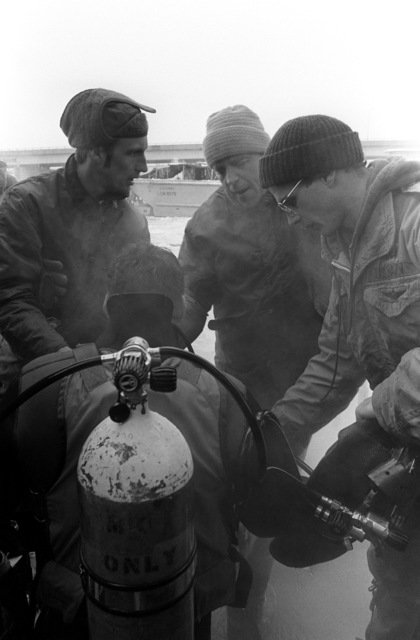 A Navy diver is assisted at the completion of his dive where he attempted to recover victims and wreckage from Flight 90, the Air Florida Boeing 737 that crashed into Rochambeau Bridge (14th Street). The divers are from the Explosive Ordnance Disposal School at Indian Head, Maryland and Harbor Clearance Unit Two, from Little Creek, Virginia