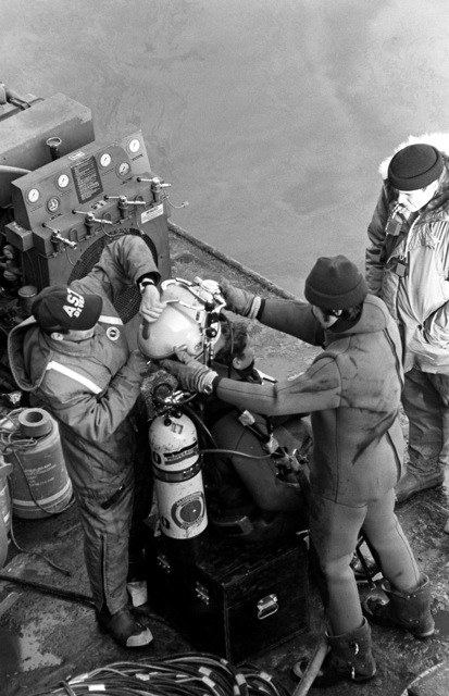A Navy diver is assisted in removing his Mark 12 gear at the completion of his dive to recover victims and wreckage from Flight 90, the Air Florida Boeing 737 that crashed into Rochambeau Bridge (14th Street). The divers are from the Explosive Ordnance Disposal School at Indian Head, Maryland and Harbor Clearance Unit Two, from Little Creek, Virginia