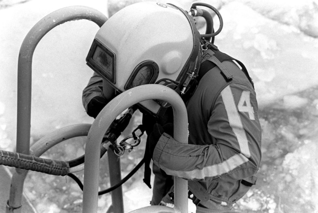 A Navy diver wearing Mark 12 dive gear prepares to enter the icy water to recover victims and wreckage from Flight 90, the Air Florida Boeing 737 that crashed into Rochambeau Bridge (14th Street). The divers are from the Explosive Ordnance Disposal School at Indian Head, Maryland and Harbor Clearance Unit Two, from Little Creek, Virginia