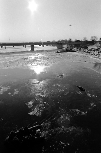A view of the icy river as Navy divers operate from the bank to recover victims and wreckage from Flight 90, the Air Florida Boeing 737 that crashed into Rochambeau Bridge (14th Street). The divers are from the Explosive Ordnance Disposal School at Indian Head, Maryland and Harbor Clearance Unit Two, from Little Creek, Virginia