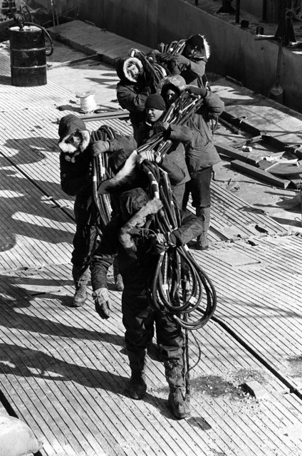 Navy dive team assistants carry oxygen tank hose onto a platform during the operation to recover victims and wreckage from Flight 90, the Air Florida Boeing 737 that crashed into Rochambeau Bridge (14th Street). The divers are from the Explosive Ordnance Disposal School at Indian Head, Maryland and Harbor Clearance Unit Two, from Little Creek, Virginia
