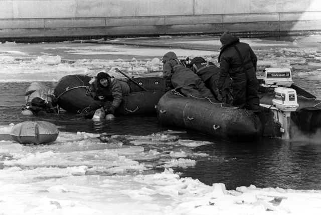 Navy divers in scuba gear, operate from rubber rafts to locate and recover victims and wreckage from Flight 90, the Air Florida Boeing 737 that crashed into Rochambeau Bridge (14th Street). The divers are from the Explosive Ordnance Disposal School at Indian Head, Maryland and Harbor Clearance Unit Two, from Little Creek, Virginia