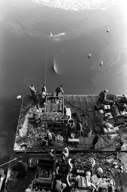 Overhead view of Navy divers operating from a platform to recover victims and wreckage from Flight 90, the Air Florida Boeing 737 that crashed into Rochambeau Bridge (14th Street). The divers are from the Explosive Ordnance Disposal School at Indian Head, Maryland and Harbor Clearance Unit Two, from Little Creek, Virginia