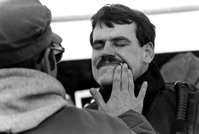 Petroleum jelly is applied to a diver's face to protect him from fuel oil and freezing temperatures during the operation to recover victims and wreckage from Flight 90, the Air Florida Boeing 737 that crashed into Rochambeau Bridge (14th Street). The divers are from the Explosive Ordnance Disposal School at Indian Head, Maryland and Harbor Clearance Unit Two, from Little Creek, Virginia