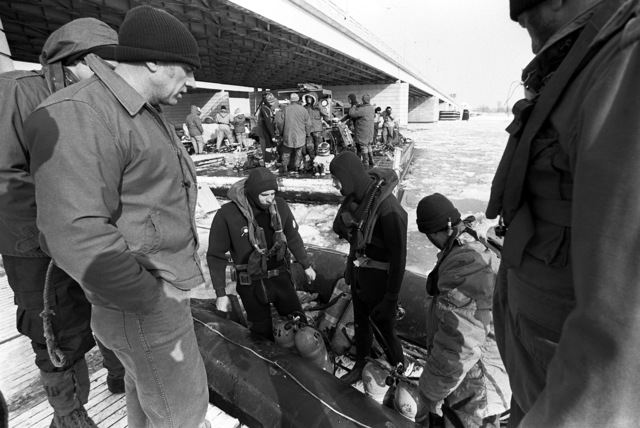 Two Navy divers in scuba gear stand in a rubber raft, before using it to locate to victims and wreckage from Flight 90, the Air Florida Boeing 737 that crashed into Rochambeau Bridge (14th Street). The divers are from the Explosive Ordnance Disposal School at Indian Head, Maryland and Harbor Clearance Unit Two, from Little Creek, Virginia