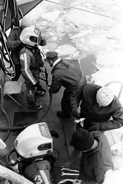 Two Navy divers wearing Mark 12 dive gear prepare to enter the icy water to recover victims and wreckage from Flight 90, the Air Florida Boeing 737 that crashed into Rochambeau Bridge (14th Street). The divers are from the Explosive Ordnance Disposal School at Indian Head, Maryland and Harbor Clearance Unit Two, from Little Creek, Virginia