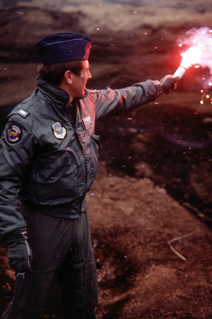 1LT David M. Loar, 345th Tactical Airlift Squadron, hold up a smoke canister to guide two C-130 Hercules aircraft over the Fuji Drop Zone, for the parachute drop of two pallets containing four 55-gallon drums of water