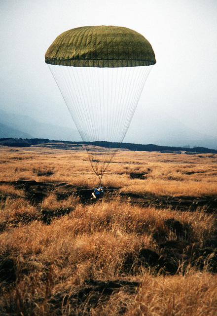 A pallet containing two 55-gallon drums of water, lands at the Fuji Drop Zone by parachute. The pallet was dropped from a C-130 Hercules aircraft