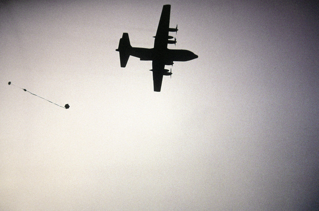 Ground-to-air silhouetted view of a C-130 Hercules aircraft dropping a pallet containing two 55-gallon drums of water, over the Fuji Drop Zone by parachute