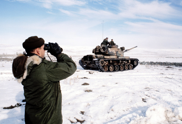 GYSGT Abbatt of Company B, 1ST Tank Battalion, uses a pair of binoculars to check the target prior to the firing of the M-60A1 tanks. The battalion is taking part in cold weather training