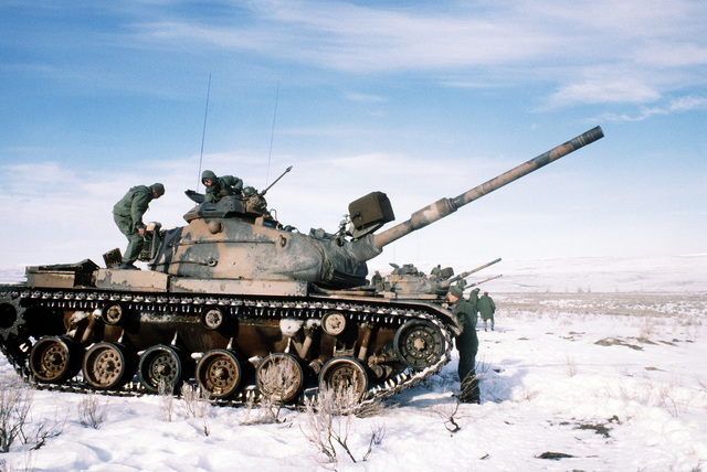 Marines from Company B, 1ST Tank Battalion, prepare to fire the 105mm gun on their M-60A1 tanks, as they start their cold weather training