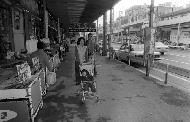 A Marine strolls past many of the stores with his wife and two children