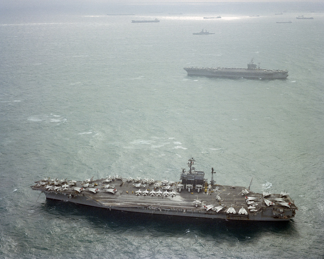 An aerial port beam view of the aircraft carrier USS JOHN F. KENNEDY (CV 67), foreground, and the nuclear-powered aircraft carrier USS DWIGHT D. EISENHOWER (CVN 69) at anchor