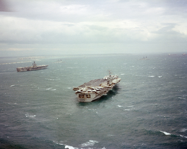 An aerial starboard quarter view of the nuclear-powered aircraft carrier USS DWIGHT D. EISENHOWER (CVN 69), right, and the aircraft carrier USS JOHN F. KENNEDY (CV 67) at anchor