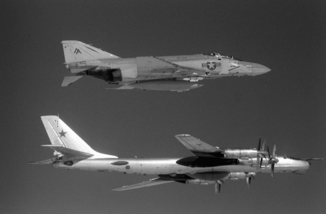 An air-to-air right side view of a U.S. Navy F-4 Phantom II aircraft, top, from Fighter Squadron 74 (VF-74) and a Soviet Tu-95 Tupolev Bear aircraft about 42 miles off the Virginia coast. The F-4 is escorting the Cuba-based Tu-95, which just penetrated the U.S. air defense zone to aerially view sea trials of the new nuclear-powered aircraft carrier CARL VINSON (CVN-70)