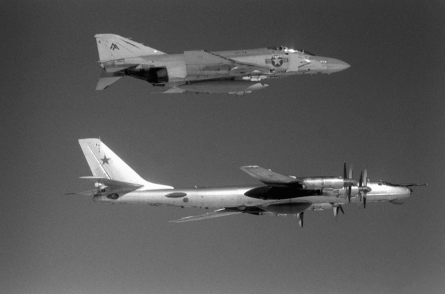 An air-to-air view of a U.S. Navy F-4 Phantom II aircraft, top, from Fighter Squadron 74 (VF-74) and a Soviet Tu-95 Tupolev Bear aircraft about 42 miles off the Virginia coast. The F-4 is escorting the Cuba-based Tu-95, which just penetrated the U.S. air defense zone to aerially view sea trials of the new nuclear-powered aircraft carrier CARL VINSON (CVN-70)