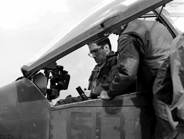 John S. Herrington, Assistant Secretary of the Navy, Manpower and Reserve Affairs, sits in the cockpit of an AH-1 Cobra helicopter during a visit to Okinawa