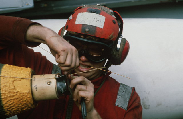 A crewman fuses a bomb prior to loading onto an aircraft on the flight deck of the aircraft carrier USS AMERICA (CV 66)