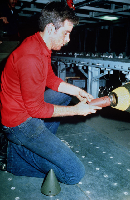 A crewman inserts a fuse into a bomb prior to loading it onto an aircraft on the flight deck of the aircraft carrier USS AMERICA (CV 66)