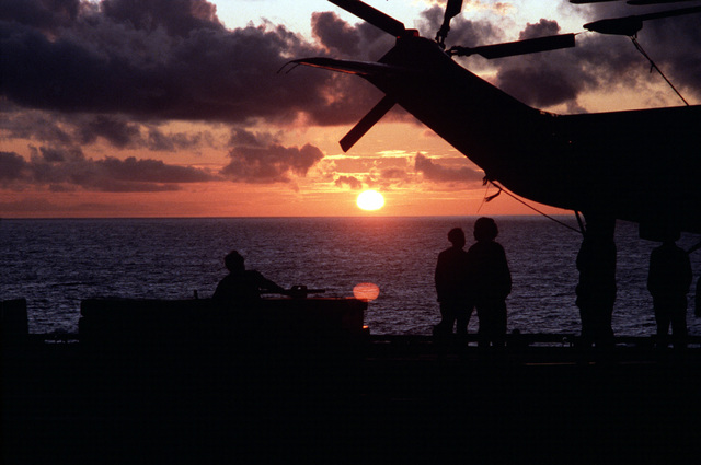 A silhouetted sunset view of crewmen performing flight deck operations aboard the aircraft carrier USS AMERICA (CV 66)