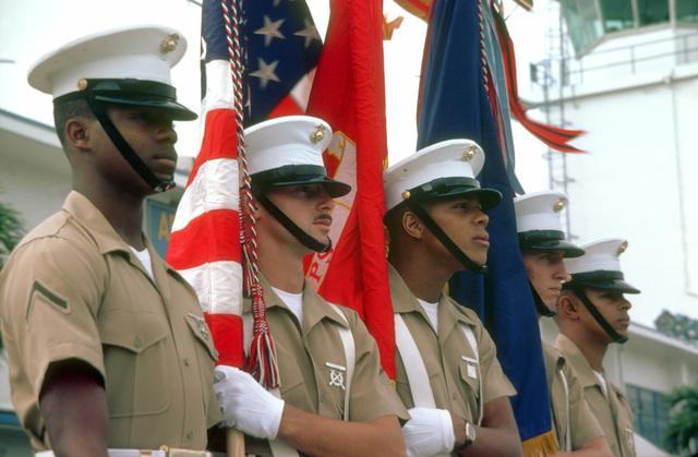 A U.S. Marine Corps color guard awaits inspection by Assistant Secretary of the Navy John S. Herrington