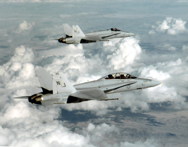 An air-to-air right side view of two F/A-18 Hornet aircraft from Fighter Attack Squadron 125 (VFA-125). The squadron is on a 23-day deployment from Naval Air Station, Lemoore, California. VFA-125 began flying the F/A-18 aircraft about 12 months ago. Squadron pilots have accumulated more than 1,500 hours in the Hornet so far