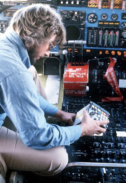 David Grant, a digital computer repairman, installs a pilot's Inertial Navigation System (INS) input terminal aboard a C-5 Galaxy aircraft
