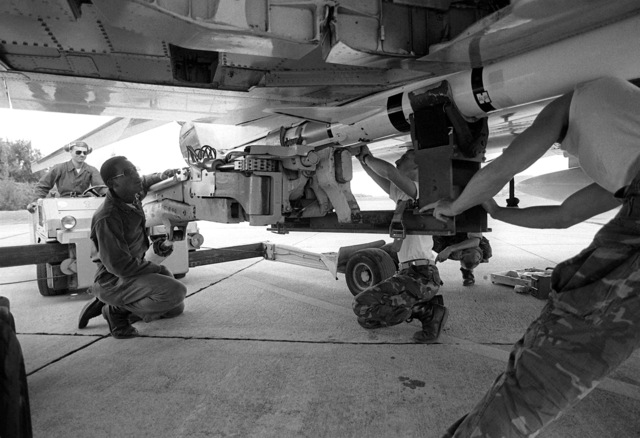 LCPL Tony Kennedy, left, from Marine Fighter Attack Squadron 235 (VMFA-235) helps load an AIM-7 Sparrow III missile aboard an F-4 Phantom II aircraft