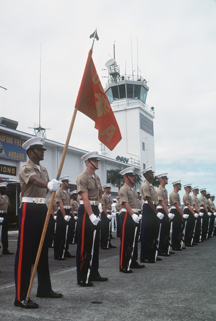 A US Marine Corps honor guard, armed with M16A1 rifles, stands at parade rest awaiting inspection by Assistant Secretary of the Navy John S. Herrington
