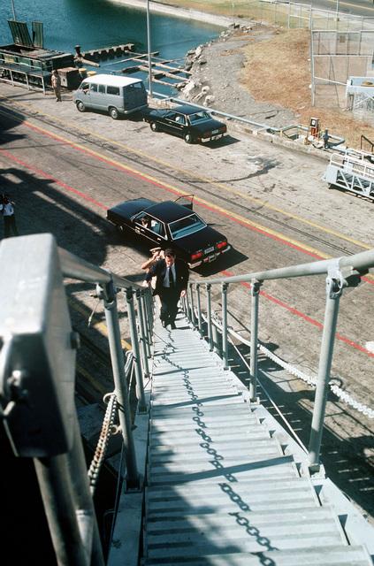 Assistant Secretary of the Navy John S. Herrington ascends the gangplank of a ship