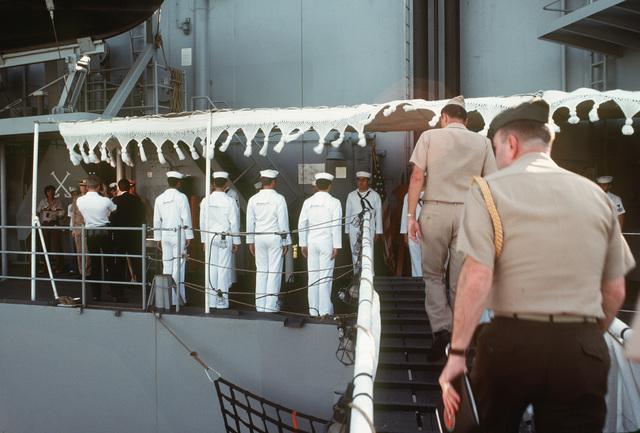 Assistant Secretary of the Navy John S. Herrington (left, dark suit) boards the destroyer USS FIFE (DD 991) for a tour