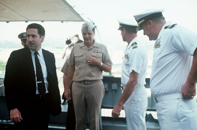 Assistant Secretary of the Navy John S. Herrington (left) tours a ship during his visit to the naval air station