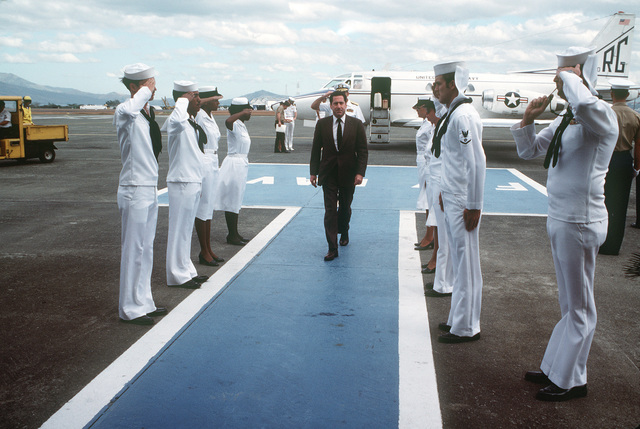 Assistant Secretary of the Navy John S. Herrington passes between sideboys upon his arrival at the naval air station. A T-39 Sabreliner aircraft is in the background