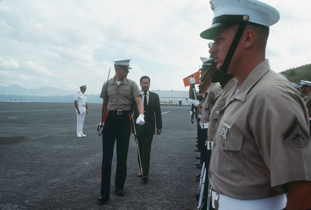 Assistant Secretary of the Navy John S. Herrington reviews a US Marine Corps honor guard, armed with M16A1 rifles, during an inspection tour