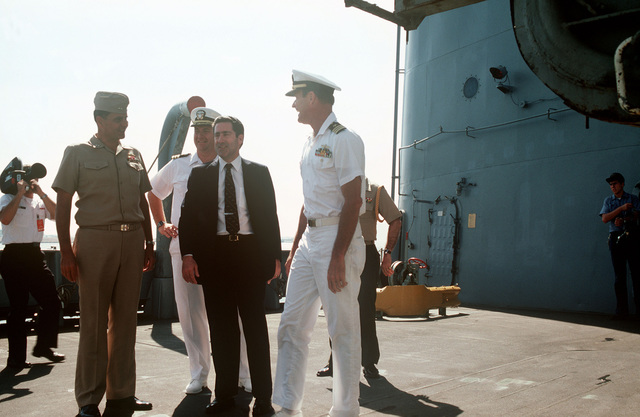 Assistant Secretary of the Navy John S. Herrington (right) speaks to Navy officers during a tour of the repair ship USS HECTOR (AR 7)