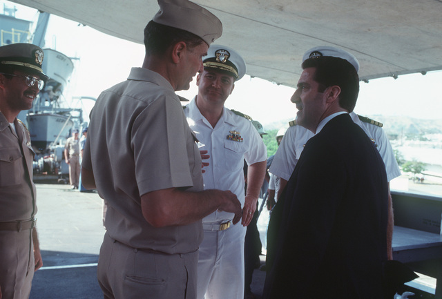 Assistant Secretary of the Navy John S. Herrington (right) talks with Navy officers during a tour of the repair ship USS HECTOR (AR 7)
