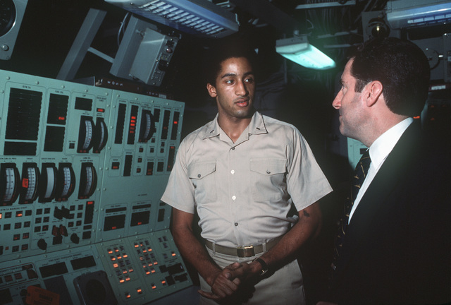 Assistant Secretary of the Navy John S. Herrington (right) tours a ship during his visit to the naval air station