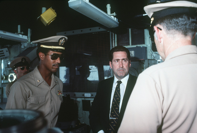 Assistant Secretary of the Navy John S. Herrington tours a ship during his visit to the naval air station