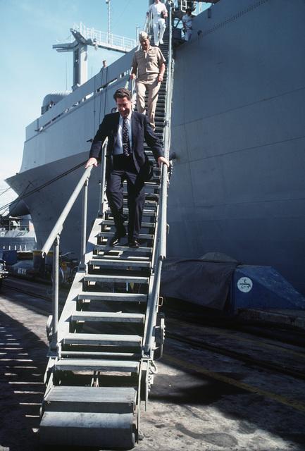 Assistant Secretary of the Navy John S. Herrington walks down a gangplank of the ammunition ship USS FLINT (AE 32) after a tour
