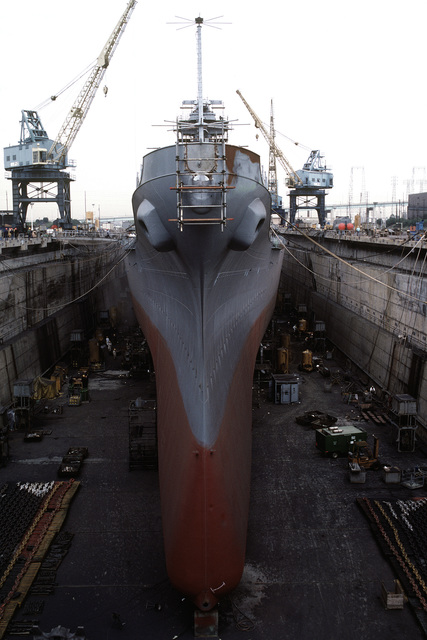 A bow view of the battleship USS NEW JERSEY (BB-62), in dry dock undergoing refitting and reactivation