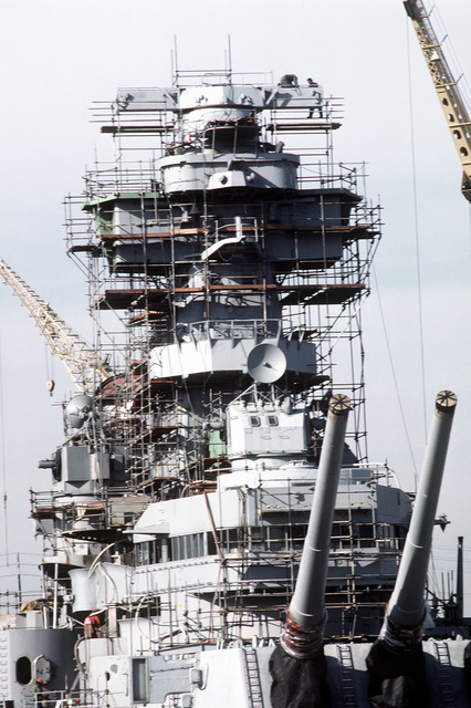 A bow view of the superstructure of the battleship USS NEW JERSEY (BB-62), surrounded by scaffolding, while being overhauled and refitted for reactivation. Note the Mark 7 16-inch/50-cal. gun turret