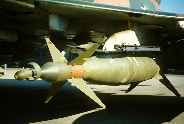 A close-up view of GBU-10 laser-guided bomb mounted under the wing of an F-4E Phantom II aircraft