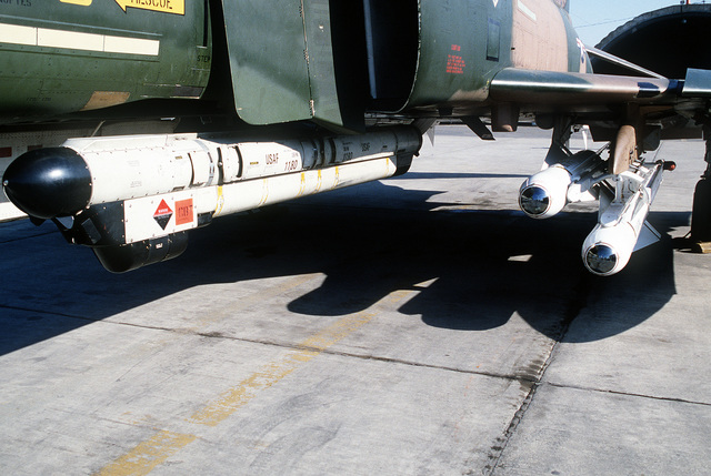A close-up view of two AGM-65 Maverick air-to-surface missiles, right, and an AN/ALQ-119 ECM Pod mounted beneath the wing of an F-4E Phantom II aircraft